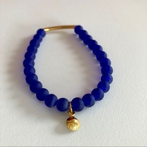 Blue glass and gold plated charm stretch bracelet